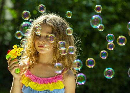 bubble. little girl blowing bubbles in the summer garden