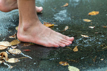 teen walks through puddles after summer rain, feet in a puddle Imagens