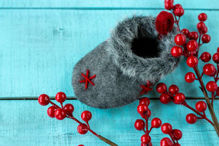 Christmas decoration sock, red berries on wooden background close-up