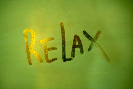 word relax written on a fogged bathroom window in partial blur, close-up