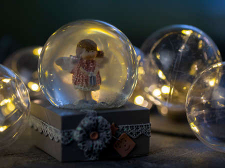 decorative snow globe with a girl angel on a dark wooden background close-up