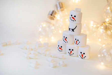 team of marshmallow snowmen on a beige background in the lighting of a garland close-up