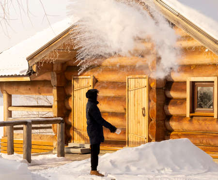 boiling water splashed out of a mug in the cold minus 35 degrees turns into steam. a teenager explores the transformation of boiling water into steam in the extreme cold, in winter Stock fotó