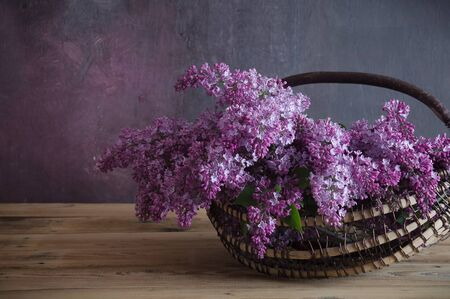 bouquet of aroma lilacs in a basket on a dark wooden background Standard-Bild