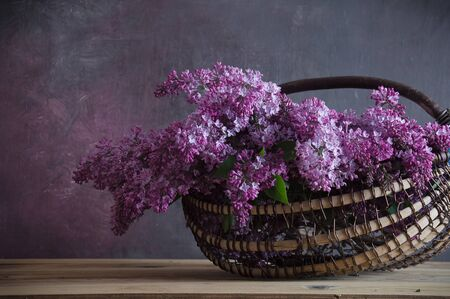bouquet of aroma lilacs in a basket on a dark wooden background
