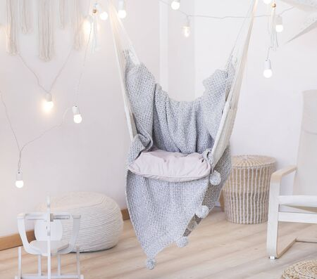 cozy hammock chair in a bright room. Pastel colors. Gray bedspread.