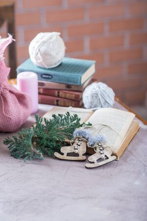 New Year and Christmas composition. An old book, a wooden toy in the form of skates.