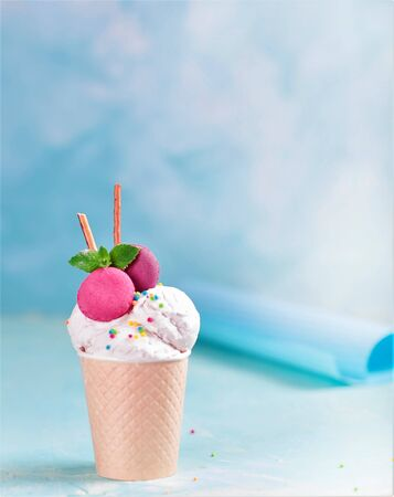 Vanilla ice cream in a paper cup on a blue, turquoise and purple background. With sweets and decorative sweet decorations.