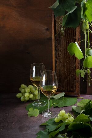 White wine in glasses. Glasses stand on a dark table next to the grape leaves and green grapes. Honeycombs stand in the background.