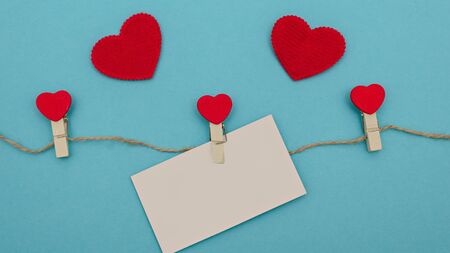 Concept for valentines day. Red hearts on a blue background. Wooden clothespins with hearts hanging on a linen cord