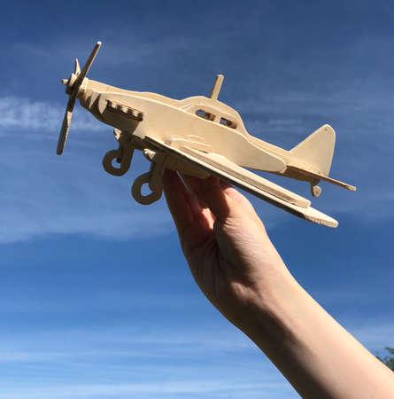 hand holding a wooden plane sky background 版權商用圖片