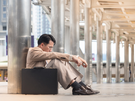 Asian businessman in a suit is worried and stressed  sitting outside office with black briefcase. Unemployment or economy concept. 版權商用圖片