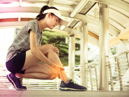 Young asian woman has legs pain, after exercise training. Lifestyle and healthy concept. Stock Photo