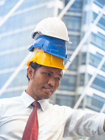 Portrait of a Powerful engineer with triple safety helmets. Engineer concept. Stock Photo