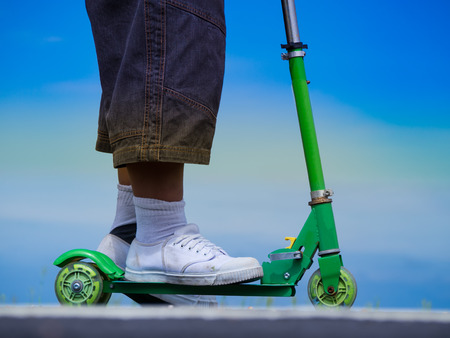 Boys big feet in white sneakers on a green scooter.