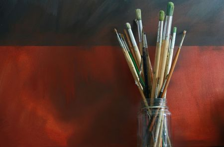 A pot of artists paint brushes in a glass jar set against an oil painted Grunge styled canvas background. Copy space available. Stock Photo