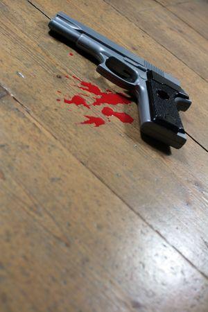 barrel pistol: Gun and blood splatters set at an agle on a wooden floor backdrop Stock Photo