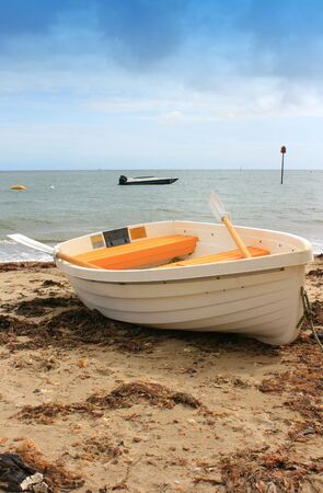 dingy: White and Yellow boat on sandy beach. Beach with washed up seaweed, sea horizon in background. Location Christchurch, Dorset UK.