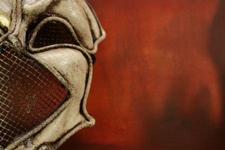 A hand made Venetian mask set to the left of a landscape image on a red grunge styled background. Copy space available.