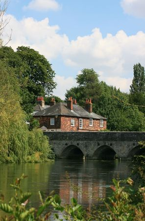 wiltshire: A view over the River Avon in Salisbury Wiltshire towards the ancient Harnham stone bridge. Reflected house in the river, greenery surrounding. Bridge celebrated in Literature and Art. Built n 1245, painted by Constabel. Stock Photo