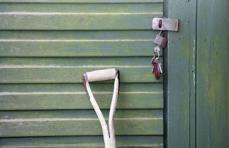 A Garden fork leaning up against a green wooden shed with a bunch of keys hanging from the shed door Stock Photo