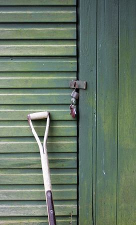 leant: A Garden fork leant up against the door of a green wooden garden shed, with a bunch of keys hanging from the shed door.