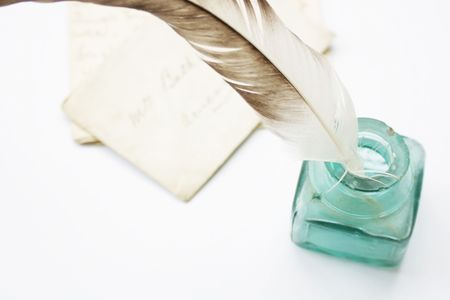 A feathered quill pen standing in a glass ink pot with old hand written letters behind, set on a white background Stock Photo