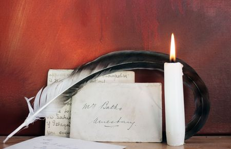 period set up of a letter quill pen and lit candle set on top
