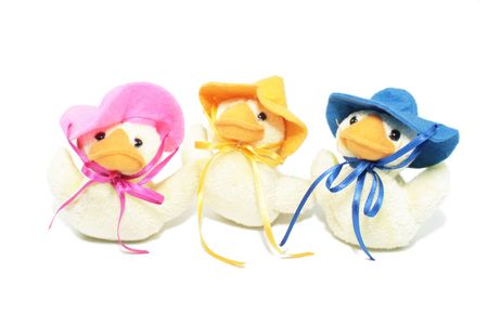 Three Easter ducklings wearing brightly coloured easter bonnets tied to their heads with ribbons. Isolated on a white background.