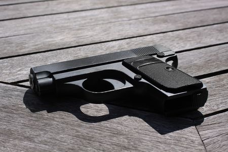 A small hand held BB gun set on a wooden slatted table top. Stock Photo