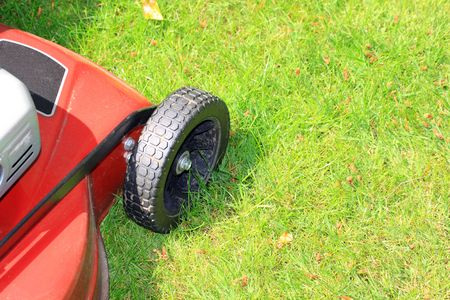A petrol driven lawn mower with rubber tyres ready to cut a green lawn. Stock Photo