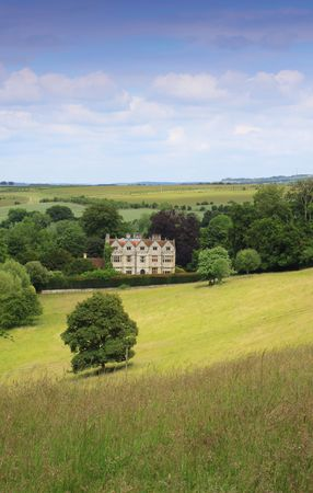 old english: Portrait format image of a country manor looking across an open rolling field to the foreground. Located in rural Wiltshire UK in a small village called Wishord Cum lake. Stock Photo
