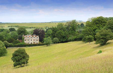 campi�a: Imagen de formato de paisaje de una mansi�n de pa�s buscando a trav�s de un campo abierto de sucesiva al primer plano. Situado en Wiltshire rural UK en un peque�o pueblo llamado Lago Cum Wishord.  Foto de archivo