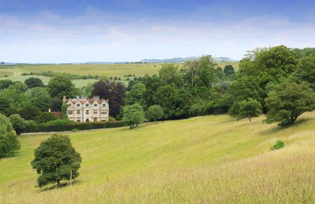 english countryside: Landscape format image of a country manor looking across an open rolling field to the foreground. Located in rural Wiltshire UK in a small village called Wishord Cum lake.