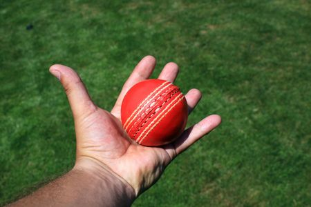 A red leather cricket ball caught in an open hand. set over a green grass area. Stock Photo