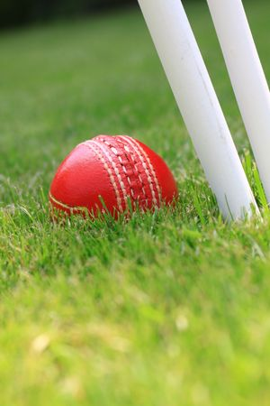 A red leather cricket ball lying in green grass behind the base of three white cricket stumps. Set on a portrait format.