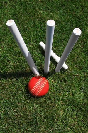 A portrait format image of a set of three white wooden cricket stumps with a red leather cricket ball at their base, with a fallen cricket bail behind. All set on green grass.