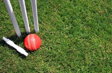 A red leather cricket ball lying in green grass at the base of three white wooden cricket stumps, and a cricket bail. Set on a landscape format.