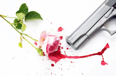 A pink rose with green stems and leaves, lying in a pool of red blood with the barrel of a gun visible. Set on a white background. Stock Photo