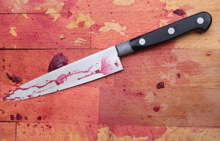A bloodied wooden butchers block with a blood stained knife.