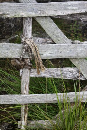 whittle: An old hand made whittle gate tied to the end of another with twine or rope. Set against a stone wall with green grass growing around.