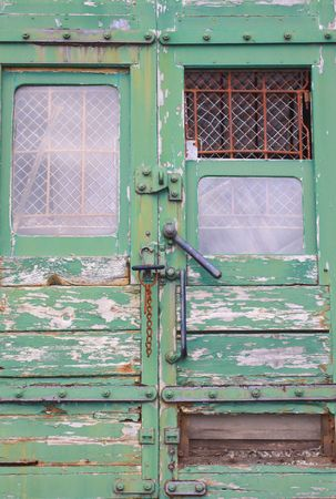 A derelict train with its door mechanism and barred and grilled windows. The entrannce to the mail section of the train.