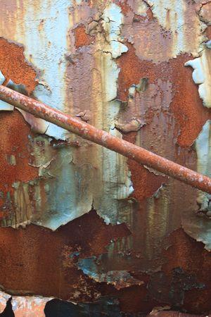 peeling paint: Fianco di una vecchia petroliera treno arrugginiti e abbandonati. Dettaglio mostra un tubo diagonale e vernice scrostata.