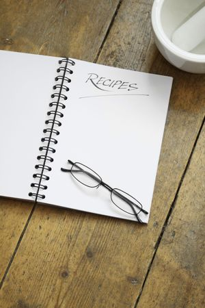 A blank wire spiral bound recipe book with the title recipe hand written at the top of the page. A pair of black framed glasses rest on the page. Set on a wooden kitchen table top with the corner of a white ceramic pestle and mortar visible in the top r