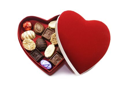 eating chocolate: A heart shaped box of chocolates with a red felt lid. Set on an isolated white background. Stock Photo