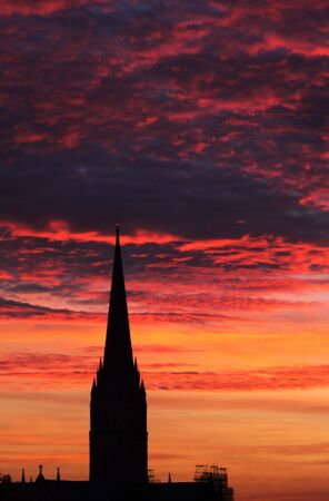 wiltshire: A portrait image of Salisbury cathedral, Wiltshire, with a winter sunset background.