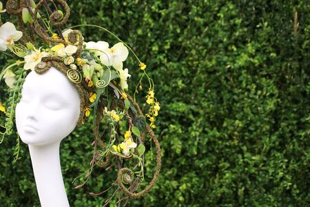 headress: A representation of a womans head adorned with a floral arrangement set against a soft focus green foliage backdrop. Twisted floral material with a variety of fresh yellow flowers creates a headress.