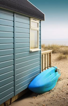 View of the side of a wooden beach hut with a blue surf board, looking towards the beach. Located in Christchurch, Dorset Hampshire UK.