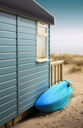 hampshire: Vista del lado de una choza de madera de la playa con un tablero de surf azul, mirando hacia la playa. Situado en Christchurch, Dorset Hampshire UK. Foto de archivo