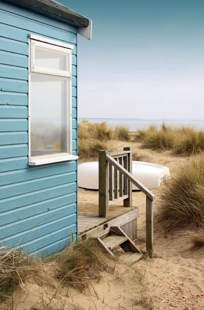 View of the side of a blue wooden beach hut with wooden terrace, looking towards the coastbeach. A white upturned boat rests in front of the hut amongst the sand and reed bushes.